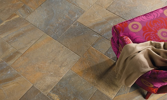 Close up of slate-look tile floor with brown, rust, and gray colors. Bright red and purple armchair visible in the corner.
