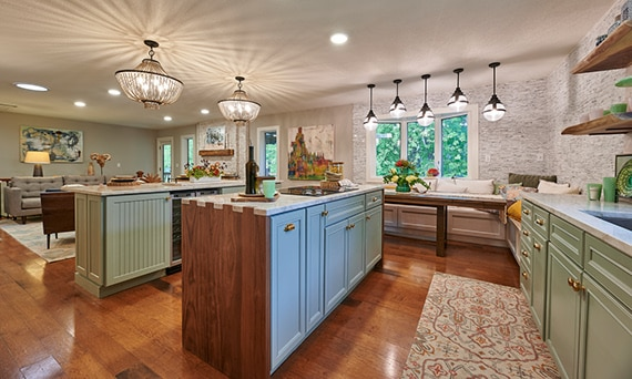 Open living and kitchen with double kitchen islands with natural quartzite countertops, wood & mint lower cabinets with brass handles, and dual chandeliers.