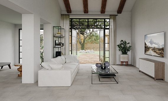 Open concept living room with white stone-look floor tile, wood beams across vaulted ceiling, white sofa, and open patio doors to the backyard.