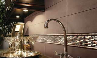 Kitchen backsplash close up with solid taupe four by twelve inch tiles and accent of mixed metals mosaic. Sink faucet and martini glasses in the foreground.
