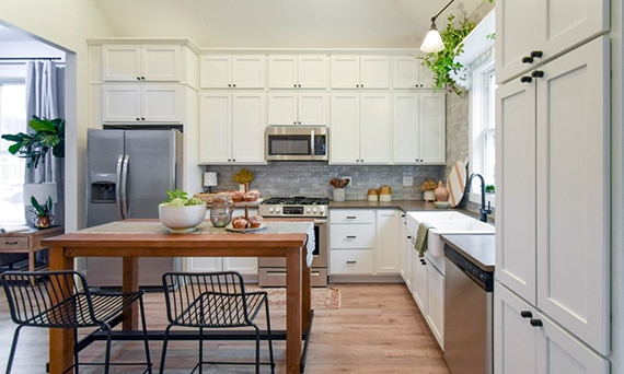 Kitchen with brown quartz countertops, cream cabinets, gray subway tile backsplash, butcherblock island, and stainless steel kitchen appliances.