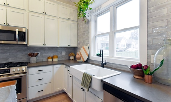 Kitchen with brown quartz countertops, dual bowl farm sink in front of two windows, cream cabinets, and gray subway tile backsplash.