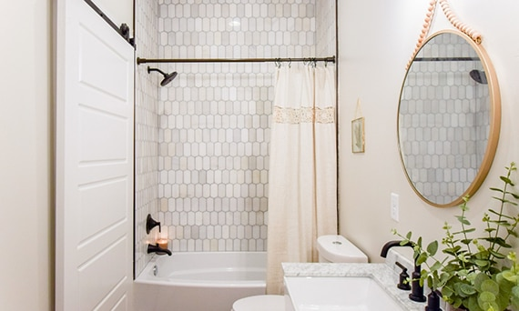 Bathroom with shower/tub with cream & gray ingot marble mosaic tile walls, white & gray marble vanity counter, and brass framed mirror.