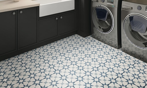 Laundry room with blue, gray, and white encaustic tiles for flooring, beige quartz countertops, farm sink, and front-loading washer & dryer.