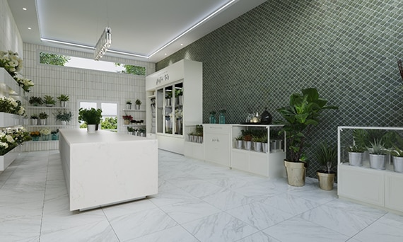 Flower shop with white floor tiles that look like marble, green arabesque mosaic wall tile, white floating shelves holding plants and flower bouquets.