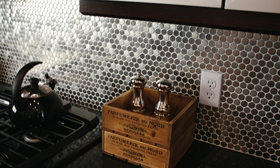 Close up of a kitchen backspalsh with penny round tiles in a stainless-steel color. Gas cooktop visible on the side with kettle. Salt and pepper shakers in an antique style box in the center.