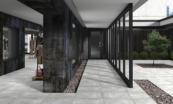 Clothing store with open courtyard of gray indoor/outdoor stone look 2CM porcelain pavers and dark metallic look porcelain slab walls.