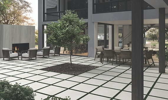 Courtyard of two-story house with dining table & chairs, outdoor fireplace & seating area, and tree in the middle of white 2CM pavers.