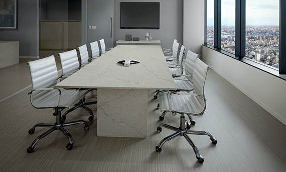Conference room with gray fabric look floor tile, long cream quartz table with gray veining, cream leather chairs, windows with a city view.