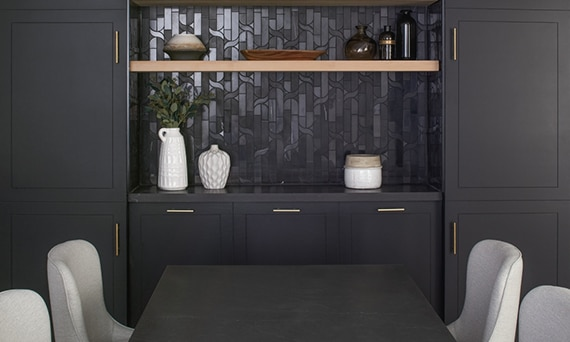Conference room with black table, white chairs, built-in with black marble mosaic wall, black marble countertop, and natural wood floating shelves.