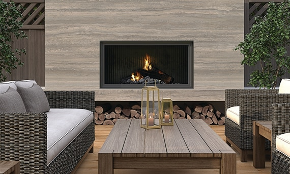 Outdoor patio fireplace with beige porcelain slab surround that looks like travertine,  wicker sofa & chair with gray cushions, and wooden coffee table.