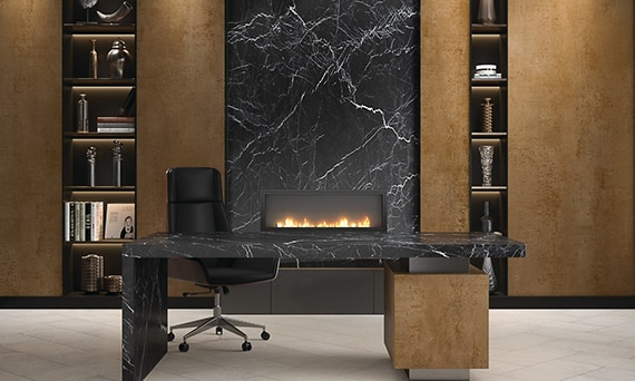 Home office with bookshelves of metallic looking porcelain slab and fireplace surround of black marble look porcelain slab, and desk made of porcelain slab that looks like black marble.