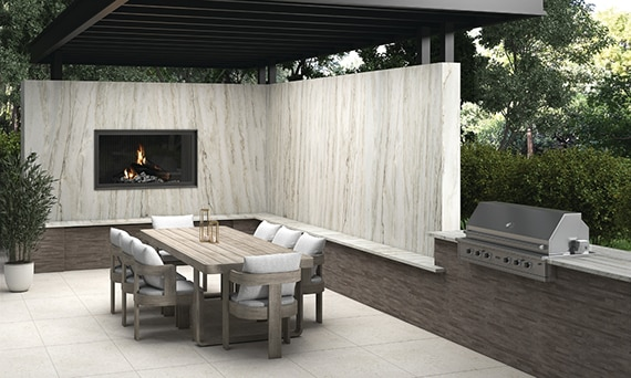 Outdoor patio with pergola, walls with natural quartzite slab, fireplace, wooden table with chairs, grill, and white stone look pavers.