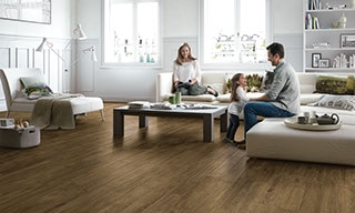Living room with wood-look porcelain tile floors, clean-lined cream furniture, and man, woman, and child playing together.