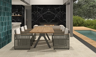 Dining room with beige stone look floor tile, aqua wall tile, black marble look porcelain fireplace surround, table & chairs, bifold glass doors open to backyard pool.