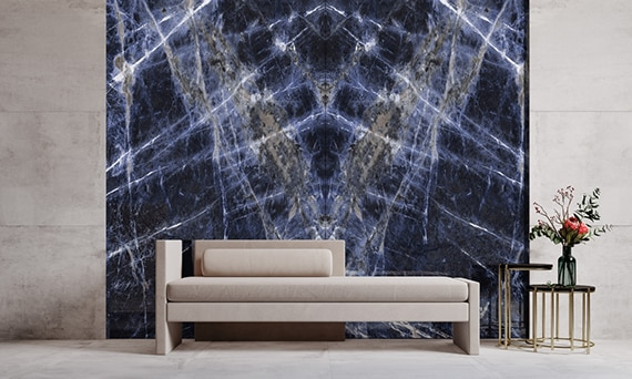 Lobby with beige marble-looking slab flooring and walls, tan chaise lounge and side table in front of large dark blue bookmatched marble-look slab with gray & white striations.