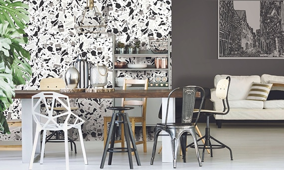 Open living room and dining room with feature wall made of white, gray, and black terrazzo look porcelain slab, table with mismatched chairs, and white sofa.