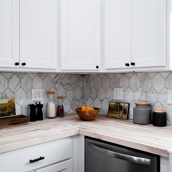 Kitchen backsplash of white & gray, Victorian mosaic marble tile, butcher block countertop, white cabinets, and stainless steel dishwasher.