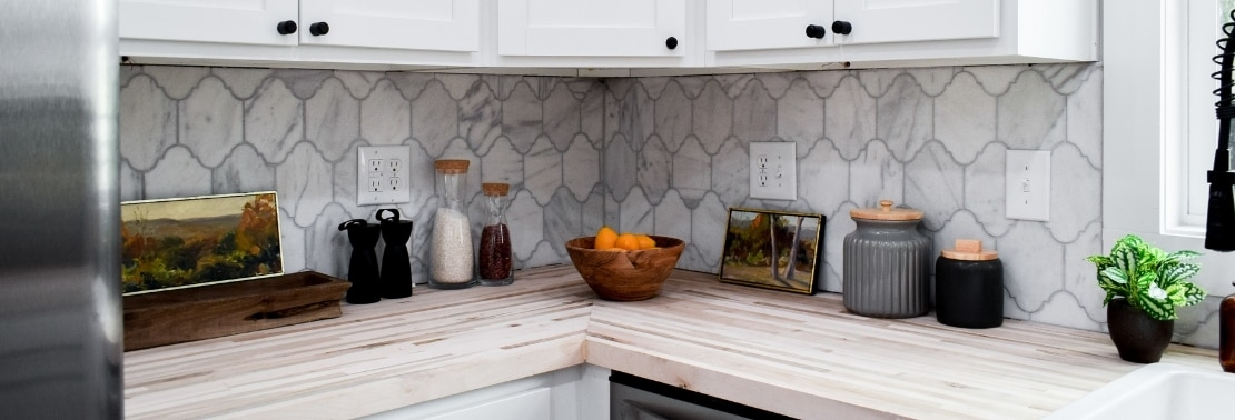 Kitchen backsplash of white & gray, Victorian mosaic marble tile, butcher block countertop, and white cabinets.