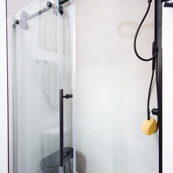 Shower with frameless barn style glass door, matte black hardware and faucet, and taupe concrete look porcelain slab walls.