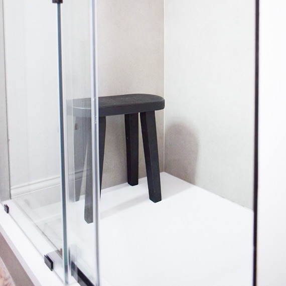 Shower with frameless barn style glass door, black stool, and taupe concrete look porcelain slab walls.
