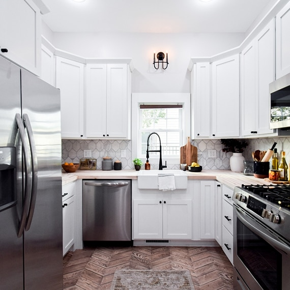 Kitchen backsplash of white & gray, Victorian mosaic marble tile, butcher block countertop, white cabinets, stainless steel refrigerator, dishwasher, gas stove and microwave.