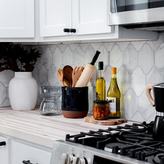 Kitchen backsplash of white & gray, Victorian mosaic marble tile, butcher block countertop, stainless steel gas stove and microwave.