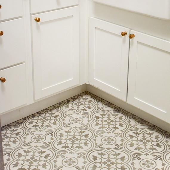 Closeup of gray and white encaustic tile in kitchen with white cabinets.