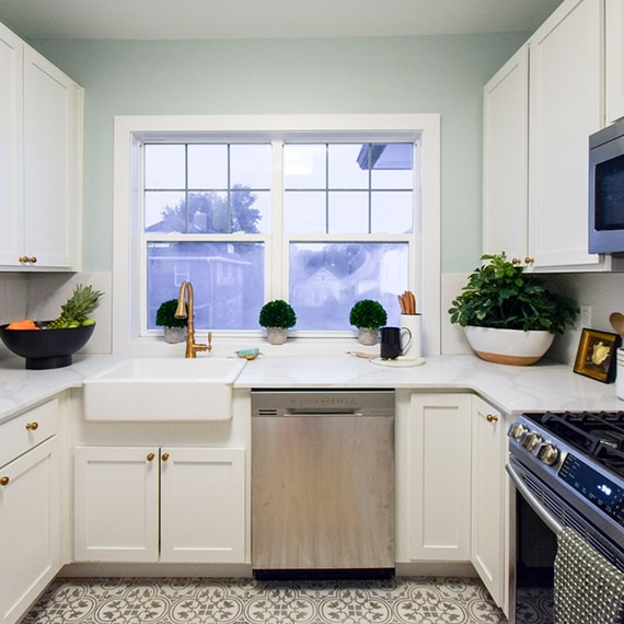 Kitchen with farm sink under picture window, marble look quartz countertops & backsplash, white & gray encaustic floor tile, and white cabinets.