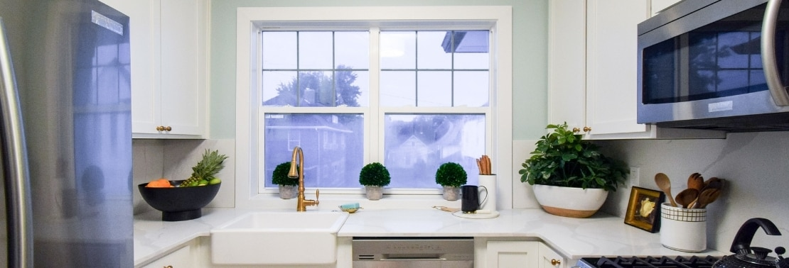 Kitchen with farm sink under picture window, marble look countertops & backsplash, and white cabinets.