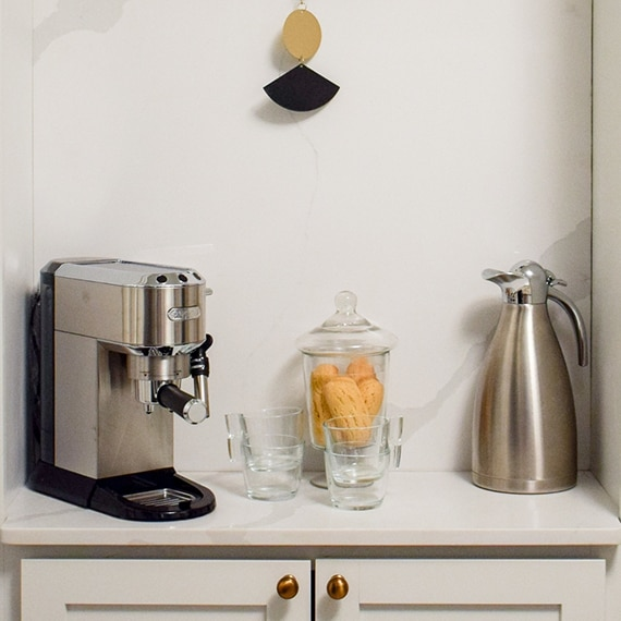 Coffee nook with marble look quartz backsplash, espresso maker, carafe, and glasses on white cabinets.