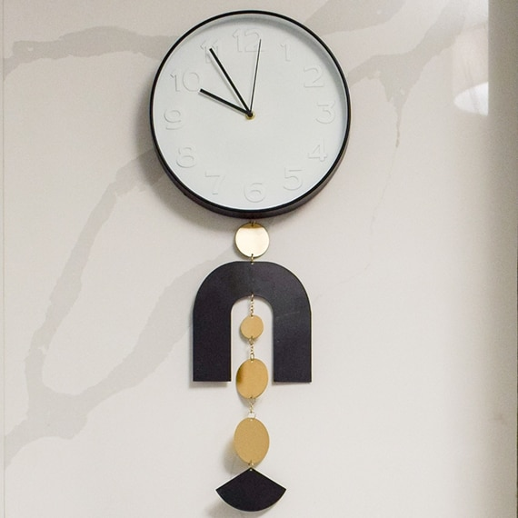 White & black wall clock with black & gold accents, hanging on a seamless marble look quartz wall.