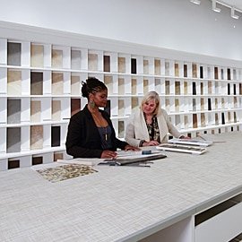 Two women looking at tile samples in a Daltile showroom.