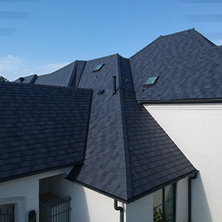 Bird's eye view of black slate-looking porcelain roofing tiles on white brick home.