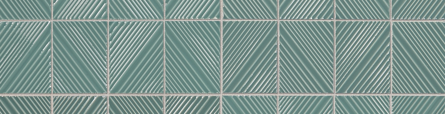 Close up of green porcelain tile with understated geometric patterns in light green that continue from tile to tile for a diamond pattern.