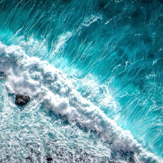Bird's eye view of aqua ocean waves crashing over rocks at the shoreline.