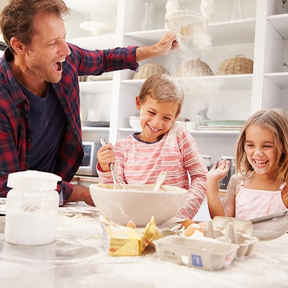 Father, son, and daughter laughing as they make homemade cookies.