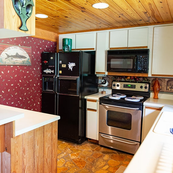 Before photo of kitchen with black refrigerator, white cabinets, red wallpaper, stone flooring, and natural wood ceiling.