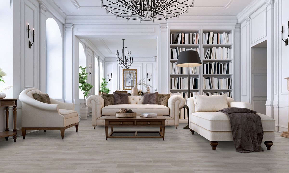 Residential library with light wood look tile flooring, white overstuffed sofa & chairs, floor-to-ceiling bookshelves, and metal chandeliers.
