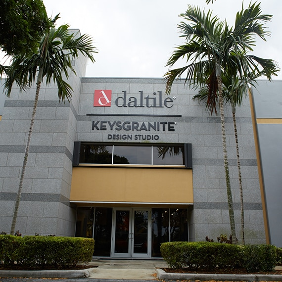 Store front of Daltile Design Studio with gray stone façade and three palm trees.