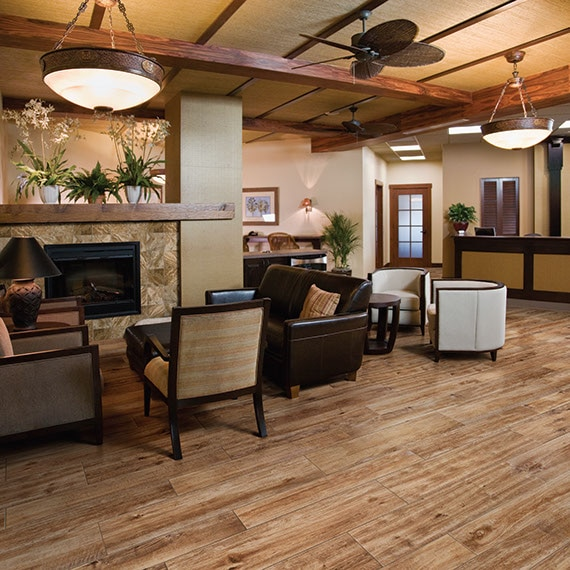A cozy lobby in brown tones with wood look tile on the floor