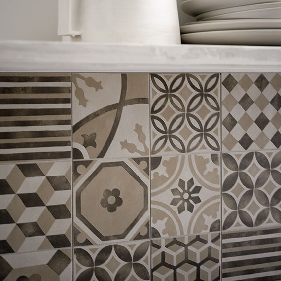 Backsplash with encaustic patterned tile and shelf with plates and a pitcher above