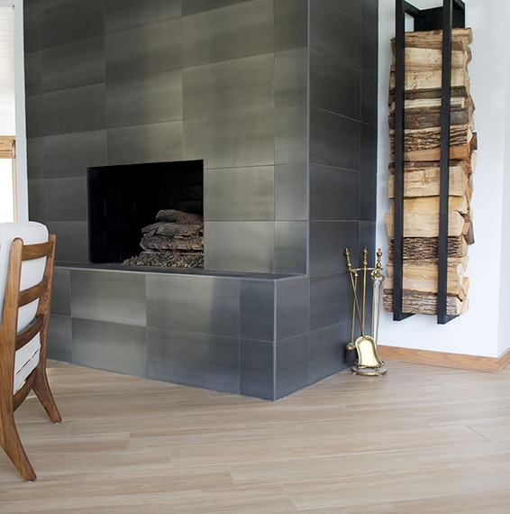 Living room with wood look tile on the floor, stone look tile on the fireplace and a wood log holder on the wall