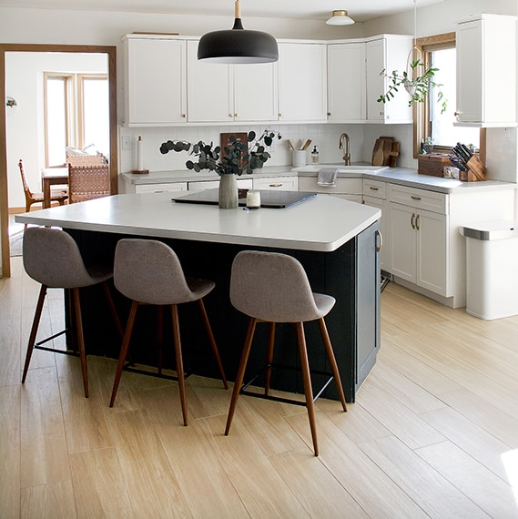 Angled kitchen with triangluar island and light wood look plank tiles on the floor