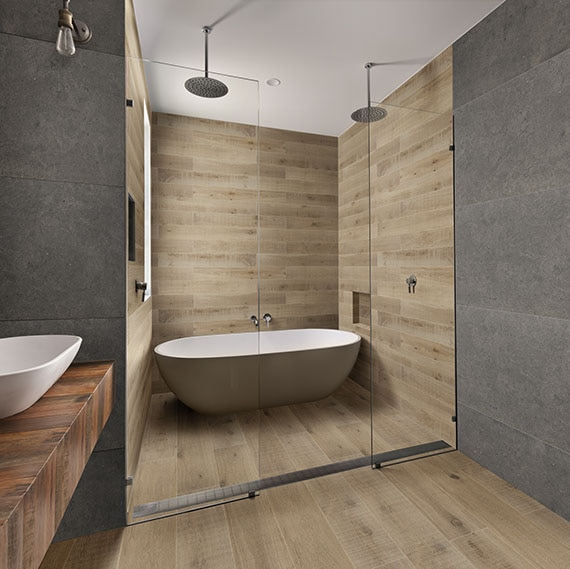 Clean lined bathroom with large format stone look tile on walls and floor and a shower with wood look plank tile