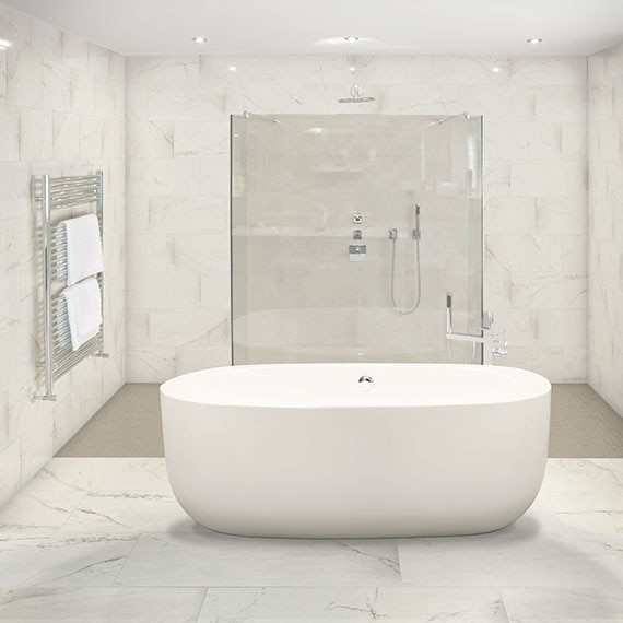 Bathroom with white marble look tile on the walls and floor and a free standing tub and glass shower