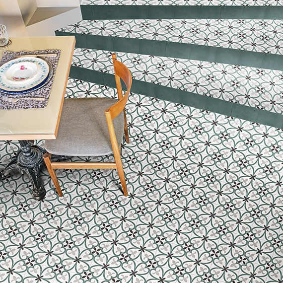 Bird's eye view of dining room floor with modern furnishings and encaustic floral pattern tile in blue and green