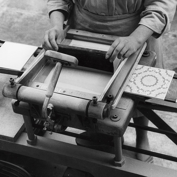 A black and white picture of a factory worker preparing encaustic tile