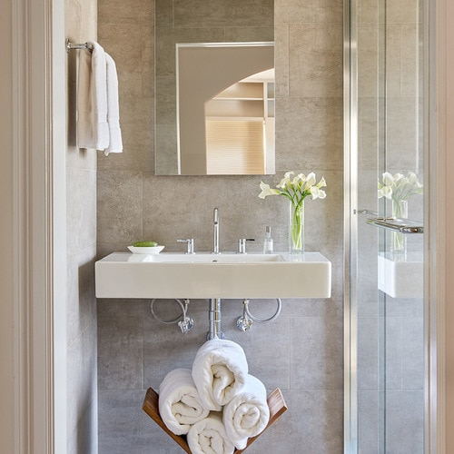 Small gray bathroom with towel rack and rolled towels under the sink