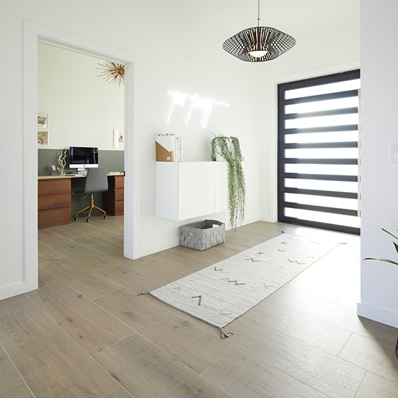 Foyer with wood look tile floor and striped rug
